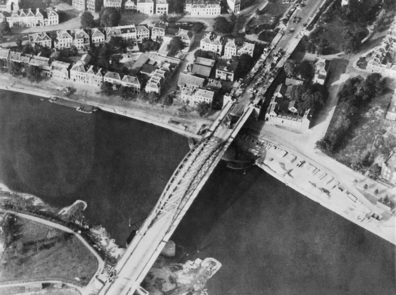 Aerial view of the bridge over the Neder Rijn, Arnhem; British troops and armoured vehicles are visible at the north end of the bridge. Had General Montgomery's ambitious scheme for seizing the Rhine bridges succeeded the war in Europe might have been shortened by many months. In the event, however, back-up forces were unable to come up quickly enough to enable the advanced airborne troops to hold the strategically vital bridge at Arnhem. © IWM (MH 2061)